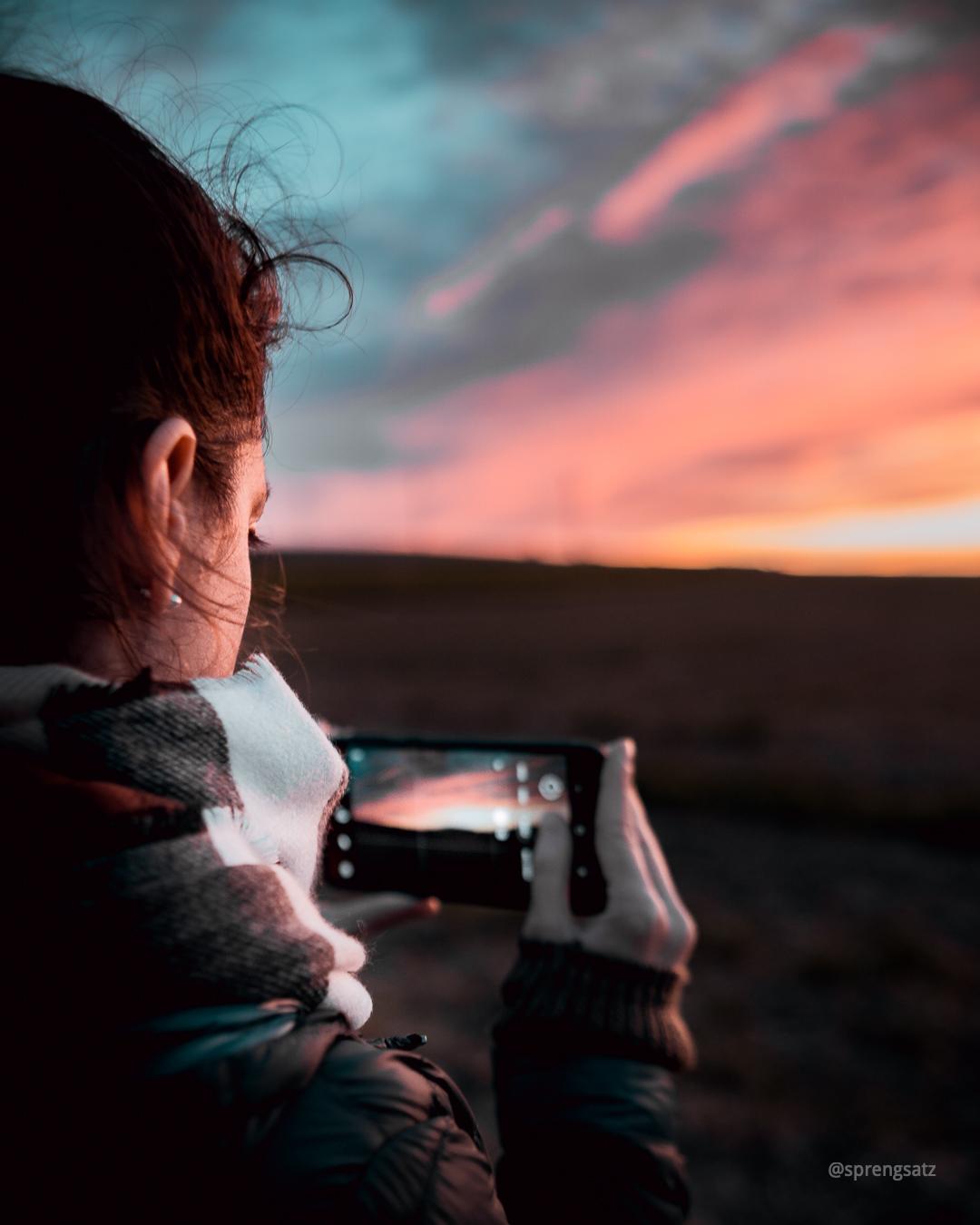 Frau mit Smartphone fotografiert den Sonnenuntergang im Zellertal (Donnersbergkreis)