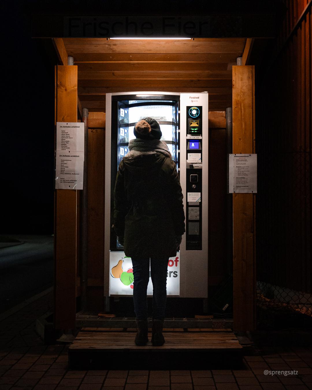 Weibliche Person vor einem beleuchteten Automaten