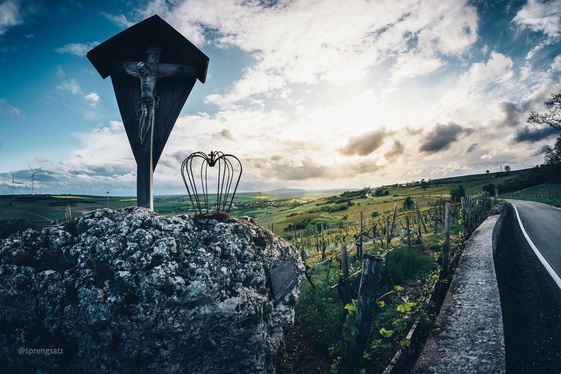 """Hölzernes Kreuz """"Zeller Schwarzer Herrgott"""" mit der dazugehörigen Weinlage im Zellertal"""