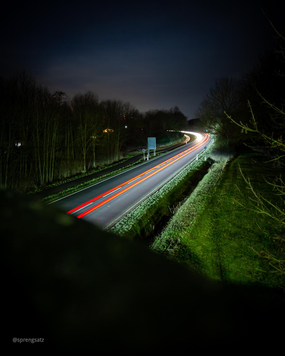 Landstraße bei Nacht mit Lichtspuren von Autolichtern