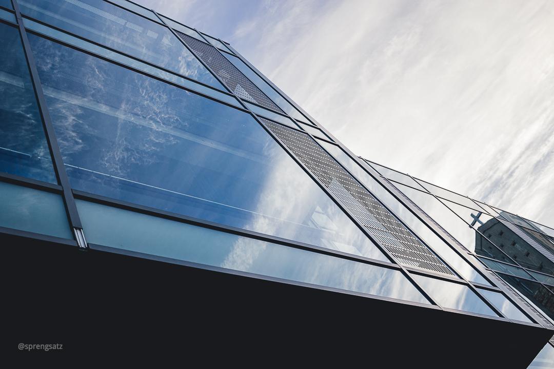 Glasfassade eines Gebäudes mit Spiegelung des Himmels und einer Kirche (Alzey)