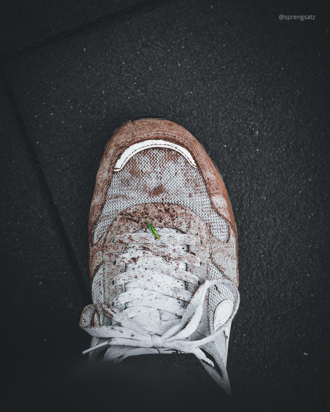 Verschmutzte Turnschuhe vom Wandern bei schlechtem Wetter