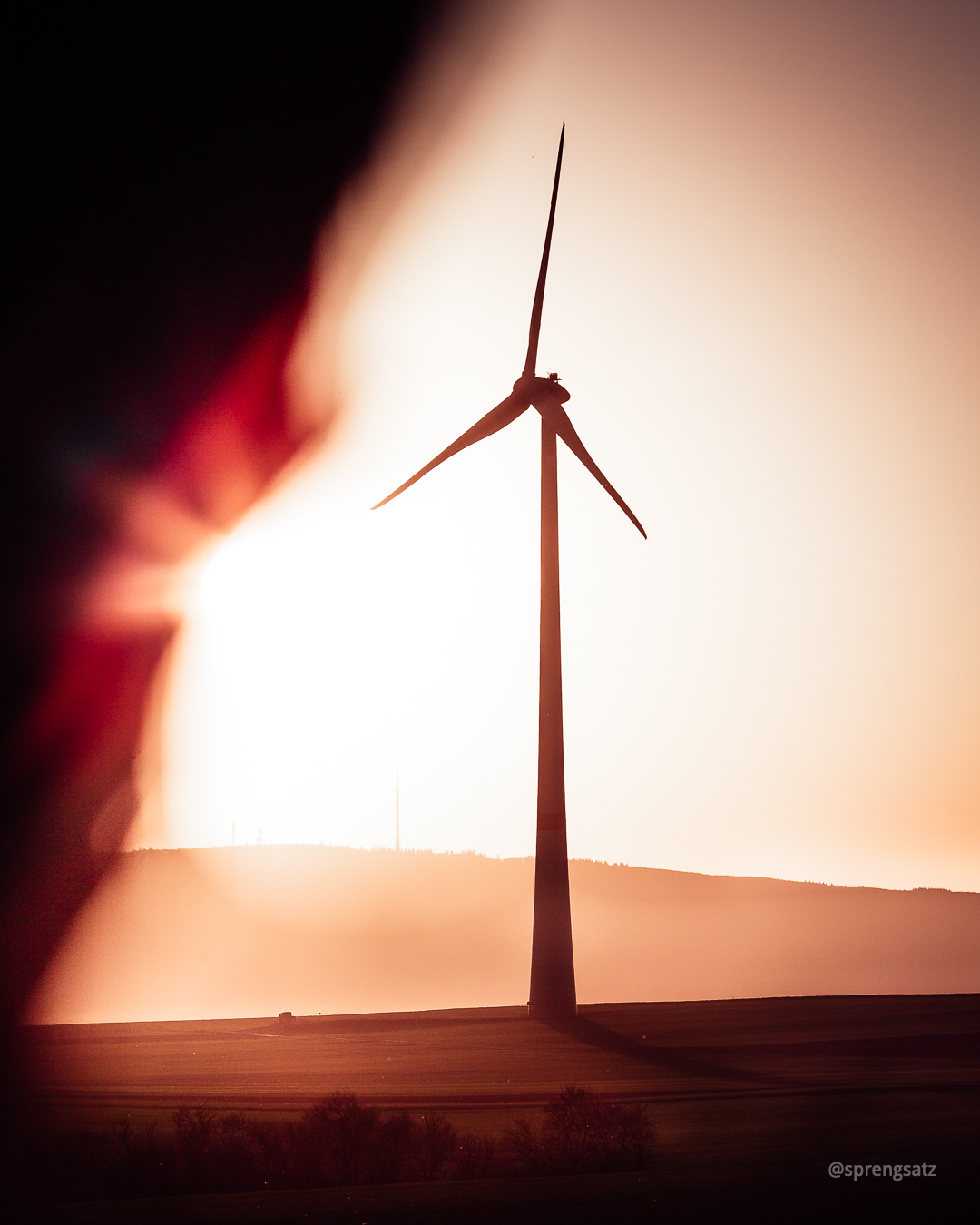 Ein Windrad vor dem Donnersberg im Sonnenlicht bei Sonnenuntergang
