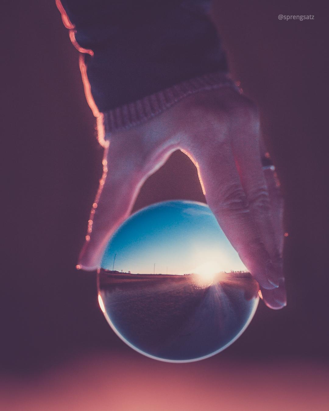 Landschaft in Kristallkugel, gehalten von der Hand einer Dame